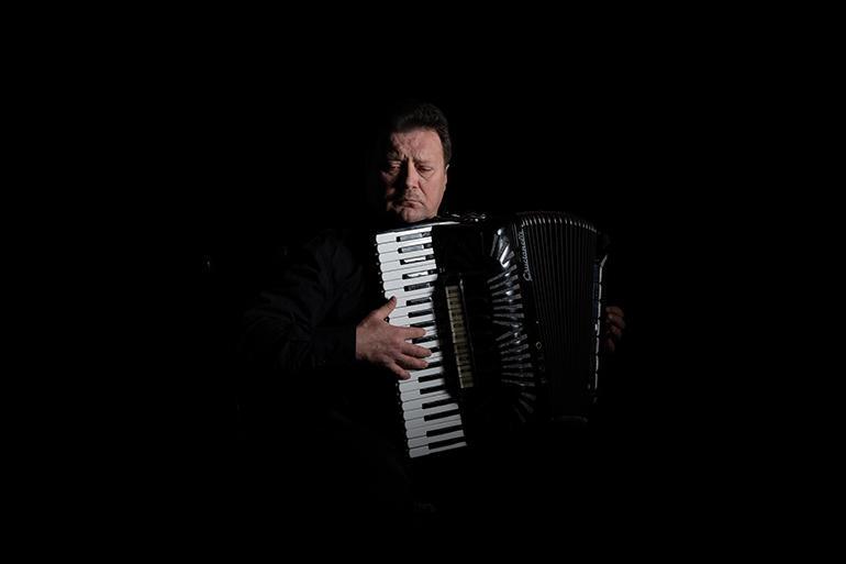 portret akordeonisty w studio w klimatycznym stylu